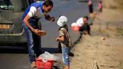 Seorang pria membeli roti tradisional yang dijajakan seorang bocah di pinggiran Algiers, Aljazair, 13 Juni 2016. Selama bulan Ramadan, sejumlah anak membantu orangtuanya menjajakan roti di kawasan ini. (REUTERS/Zohra Bensemra)
