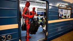 Penari underground yang mengenakan kostum Spiderman membawa tas mereka di kereta bawah tanah Saint Petersburg, pada 21 Mei 2021. Penamplan khusus penari Rusia tersebut membuat sejumlah penumpang yang berada di dalam subway kaget dan terhibur. (Olga MALTSEVA / AFP)