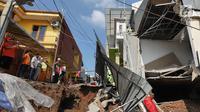 Sejumlah warga melihat kondisi tanah longsor di Perumahan Pesona Kalisari, Pasar Rebo, Jakarta, Selasa (27/11). Intensitas hujan yang tinggi mengakibatkan sebidang tanah di wilayah tersebut longsor. (Liputan6.com/Herman Zakharia)