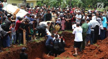 Suasana pemakaman korban kecelakaan Tanjakan Emen di Tempat Pemakaman Umum (TPU) Legoso, Tangerang Selatan, Banten, Minggu (11/2). Pemakaman dilakukan secara massal. (Liputan6.com/JohanTallo)