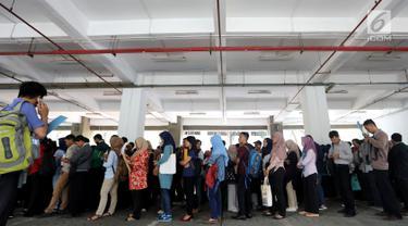 Peserta mengantre untuk pendaftaran ulang ujian CPNS Kementerian Kelautan dan Perikanan (KKP) di kawasan Gambir,  Jakarta, Minggu (8/10). Pendaftaran ujian CPNS ini untuk menempati berbagai formasi di KKP. (Liputan6.com/Johan Tallo)