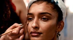Seorang model India saat dirias oleh kru makeup di belakang panggung sebelum tampil di catwalk selama Lakmé Fashion Week (LFW) Summer Resort 2019 di Mumbai, India (31/1). (AFP Photo/Sujit Jaiswal)
