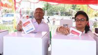 Wali Kota Jayapura, Behur Tomi mano dan istri melakukan pencoblosan di TPS 12, Distrik Abepura, Kota Jayapura, Papua. (Liputan6.com/Katharina Janur)