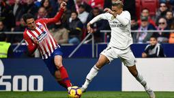 Bek Atletico Madrid, Santiago Arias berusaha merebut bola yang dibawa striker Real Madrid, Mariano selama pertandingan lanjutan La Liga Spanyol di stadion Wanda Metropolitano (9/2). Real Madrid menang 3-1 atas Atletico. (AFP Photo/Pierre-Philippe Marcou)