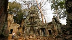 Wisatawan mengunjungi kompleks kuil Ta Prohm di provinsi Siem Reap, Kamboja. Kuil yang dibangun dalam gaya arsitektur Bayon pada sekitar akhir abad ke-12 ini masuk kedalam daftar situs Warisan Dunia UNESCO pada tahun 1992. (REUTERS/Samrang Pring)