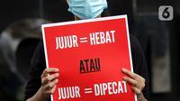 Peserta aksi dari Koalisi Masyarakat Sipil AntiKorupsi membawa poster saat berunjukrasa di depan Gedung KPK Jakarta, Selasa (18/5/2021). Dalam aksinya mereka memberi dukungan kepada 75 pegawai KPK yang dinyatakan tidak lulus TWK dalam tahap alih status kepegawaian. (Liputan6.com/Helmi Fithriansyah)