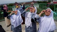 Sejumlah peserta nobar sedang mengamati gerhana matahari dengan menggunakan kacamata khusus di Observatrim Assalaam, Kamis (26/12).(Liputan6.com/Fajar Abrori)