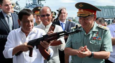 Presiden Filipina Rodrigo Duterte bersama Menhan Rusia, Sergei Shoigu (kanan) memegang senapan serbu AK-47 sumbangan dari Rusia di atas kapal perusak Rusia Admiral Panteleyev di pelabuhan Metro Manila, Filipina (25/10). (AFP Photo/Robinson Ninal)