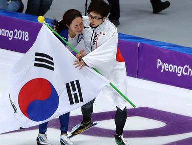 Peraih medali emas, skater Nao Kodaira dari Jepang memeluk dan menghibur peraih perak, skater Lee Sang Hwa dari Korea Selatan setelah cabang skating speed 500 meter putri di Olimpiade Musim Dingin Pyeongchang 2018, Minggu (18/2). (AP/Eugene Hoshiko)