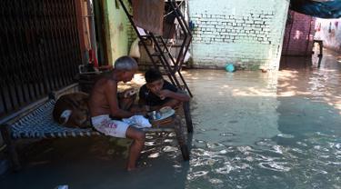 Seorang pria dan anak laki-laki makan di atas bangku saat banjir melanda daerah perumahan dekat tepi Sungai Yamuna yang meluap di New Delhi, India, Selasa (20/8/2019). (AFP Photo/Sajjad Hussain)