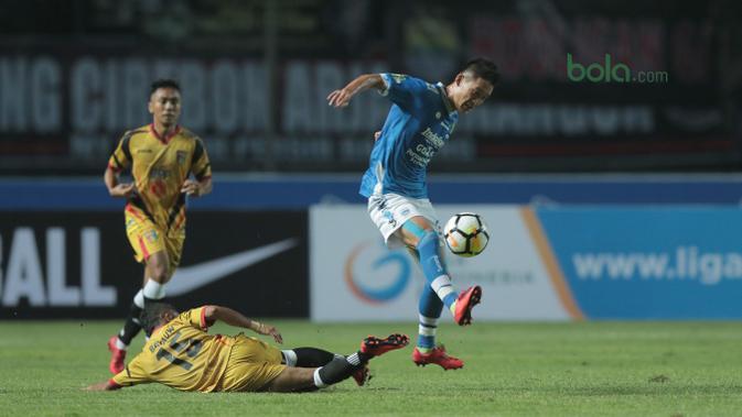 Pemain Persib Bandung, Oh In-kyun menghinari terjangan pemain Mitra Kukar, Hendra Bayauw pada laga Liga 1 Indonesia di GBLA, (8/4/2018). (Bola.com/Nick Hanoatubun)