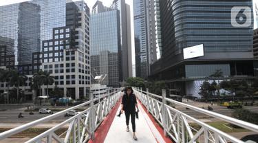 Pejalan kaki melintas di jembatan penyeberangan orang (JPO) yang tidak beratap di jalan Sudirman, Jakarta, Rabu (6/11/2019). Pemprov DKI melalui Dinas Bina Marga mencopot atap JPO Sudirman agar pejalan kaki dapat menikmati pemandangan gedung-gedung pencakar langit. (merdeka.com/Iqbal Nugroho)