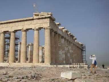 Seorang pria mengambil gambar Kuil Parthenon di Bukit Acropolis, Athena, Yunani, Senin (18/5/2020). Yunani kembali membuka kota kuno Acropolis serta situs-situs lainnya setelah dua bulan ditutup selama lockdown akibat pandemi virus corona COVID-19. (AP Photo/Petros Giannakouris)