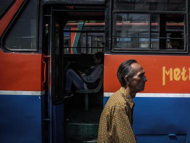 Seorang pria melintas diantara Metromini di Terminal Blok M, Jakarta, Rabu (26/7). Dinas Perhubungan (Dishub) DKI Jakarta akan merevitalisasi 700 unit metromini menjadi Minitrans. (Liputan6.com/Faizal Fanani)