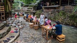 Pelanggan makan siang di restoran dengan meja di aliran sungai di Kampung Kemensah di pinggiran Kuala Lumpur pada 14 Juli 2020.(Mohd RASFAN / AFP)