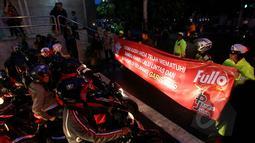 Petugas kepolisian Satlantas Jakarta Pusat membentangkan spanduk sosialisasi larangan berhenti pada garis stop di kawasan Cideng, Jakarta, Senin (23/2). (Liputan6.com/Johan Tallo)