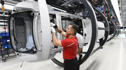 Mekanik melakukan pengecekan rangka mobil listrik Porsche Taycan saat proses perakitan di pabrik perusahaan Porsche AG di Stuttgart, Jerman, Rabu (4/3/2020). Porsche Taycan merupakan mobil bertenaga listrik pertama  dari pembuat mobil mewah Jerman, Porsche AG. (AFP Photo/Thomas Kienzie)