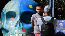 "Seorang pria berpose dengan tengkorak yang dihias selama pameran edisi keempat ""Mexicraneos"" (Mexisculls) di Reforma Avenue, Mexico City pada 23 Oktober 2020. Instalasi sebanyak 55 tengkorak berbagai warna tersebut menghiasi jalanan sebagai bagian dari perayaan Day of the Dead (ALFREDO ESTRELLA/AFP)"