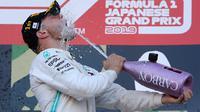 Pembalap Mercedes, Valtteri Bottas menuangkan sampanye untuk dirinya sendiri di atas podium setelah menjuarai balapan Formula 1 (F1) GP Jepang di Sirkuit Suzuka, Minggu (13/10/2019). Bottas menjadi pembalap pertama yang menyentuh garis finis usai melakoni lomba 53 putaran. (AP/Toru Takahashi)
