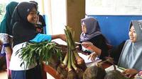 Senyum calon siswa sekolah alam MTs Pakis, Cilongok, Banyumas mengembang menerima kartu registrasi hanya dengan membayar memakai hasil bumi. (Foto: Liputan6.com/Muhamad Ridlo)