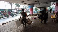 Petugas Satpol PP melakukan razia kepada para tunawisma di bawah flyover Jatinegara, Jakarta Timur, Senin (19/7/2021). Razia ini merupakan upaya dari Kecamatan Jatinegara di kawasan Kampung Melayu untuk bersih dari tunawisma yang sering tidur dan berjualan.  (Liputan6.com/Johan Tallo)