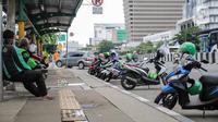 Sejumlah pengemudi ojek online beristirahat di sebuah halte di kawasan Harmoni, Jakarta, Selasa (7/4/2020). Selama pemberlakuan Pembatasan Sosial Berskala Besar (PSBB), layanan ojek online (ojol) akan dilarang mengangkut penumpang dan hanya dibolehkan untuk antar barang. (Liputan6.com/Faizal Fanani)