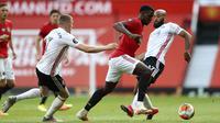 Gelandang Manchester United, Paul Pogba, berusaha melewati pemain Sheffield United pada laga Premier League di Stadion Old Trafford, Rabu (24/6/2020). Manchester United menang dengan skor 3-0. (AP/Michael Steele)