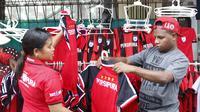 Sejumlah warga berebut membeli jersey  dan kaos tim Persipura di Kawasan Taman Imbi, Jayapura, Jumat (29/4/2016). (Bola.com/Nicklas Hanoatubun)