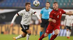Penyerang Jerman, Luca Waldschmidt, berebut bola dengan bek Republik Ceko, Jakub Brabec, pada laga uji coba di RB Arena, Kamis (12/11/2020) dini hari WIB. Jerman menang 1-0 atas Republik Ceko. (AFP/Odd Andersen)