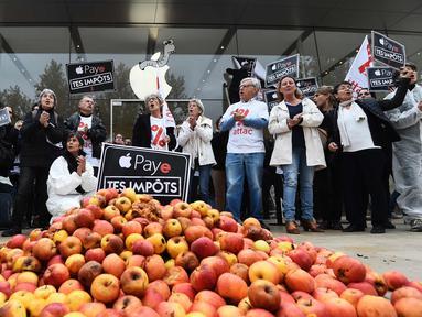 """Aktivis ATTAC berada di dekat apel dan tulisan """"bayar pajak anda"""" berunjuk rasa di luar toko Apple saat peluncuran iPhone X di Aix-en- Provence, Prancis (3/11). Unjuk rasa ini menentang penghindaran pajak oleh Apple. (AFP Photo/Anne-Christine Poujoulat)"""