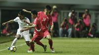 Gelandang Indonesia, Febri Hariyadi, berusaha melewati pemain Korea Utara pada laga PSSI Anniversary Cup 2018 di Stadion Pakansari, Senin (30/4/2018). Skor berakhir imbang 0-0. (Bola.com/M Iqbal Ichsan)