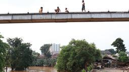 Anak-anak bersiap melompat ke Sungai Ciliwung yang meluap di kawasan Rawajati, Jakarta, Jumat (26/4). Tingginya volume debit air yang berasal dari Bogor tidak menyurutkan niat anak-anak itu untuk tetap berenang, meskipun berbahaya bagi keselamatan. (Liputan6.com/Immanuel Antonius)