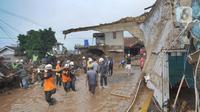 Tim SAR gabungan TNI, Polri, dan relawan membersihkan material longsor usai banjir bandang menerjang Kampung Cibuntu, Desa Pasawahan, Kecamatan Cicurug, Sukabumi, Selasa (22/9/2020). Banjir mengakibatkan puluhan bangunan rusak berat, 12 rumah hanyut, dan dua korban hilang. (merdeka.com/Arie Basuki)