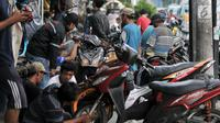 Montir memperbaiki motor di bengkel di Jalan Otista, Jakarta, Minggu (26/5/2019). Jelang Idul Fitri atau Lebaran, jumlah pelanggan bengkel motor di kawasan Otista meningkat, mulai dari menyervis mesin hingga membeli perlengkapan guna kesiapan mudik mendatang. (merdeka.com/Iqbal S. Nugroho)