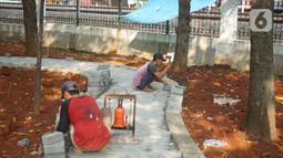 Pekerja menyelesaikan pembuatan jogging track di Taman Citra PPSU Srengseng Sawah, Jakarta, Rabu (4/12/2019). Jogging track tersebut dibuat guna meningkatkan kenyamanan bagi warga yang ingin beraktivitas di taman tersebut. (Liputan6.com/Immanuel Antonius)