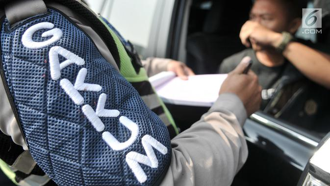 Polisi menilang pengendara yang melanggar pemberlakuan perluasan sistem ganjil genap di Jalan Salemba Raya, Jakarta, Senin (9/9/2019). Perluasan sistem ganjil genap kendaraan bermotor mulai diberlakukan hari ini. (Dailymail.co.id/Iqbal Nugroho)