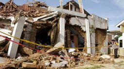 Seorang polisi memeriksa rumah yang runtuh gempa magnitudo 5,1  di Sukabumi, Jawa Barat (10/3/2020). Hasil analisis mekanisme sumber menunjukkan bahwa gempabumi memiliki mekanisme pergerakan mendatar (Strike-Slip Fault). (AFP/Wulung Widarba)