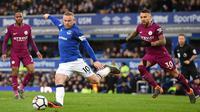 Striker Everton Wayne Rooney melakukan tendangan saat melawan Manchester City dalam pertandingan Liga Inggris di Goodison Park di Liverpool (31/3). Kemenangan ini membuat Manchester City makin dekat meraih gelar juara Premier League.(AFP Photo/Paul Ellis)