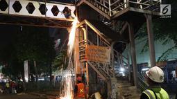 Pekerja melakukan proses pemotongan rangka utama Jembatan Penyeberangan Orang Pasar Minggu, Jakarta, Sabtu (6/4). JPO Pasar Minggu akan dibangun kembali dengan konsep lebih futuristik serta ramah disabilitas. (Liputan6.com/Helmi Fithriansyah)