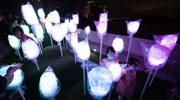 Orang-orang menikmati pemandangan malam di Festival Cahaya Makau 2020 yang digelar di Tap Seac Square, Makau, China selatan, pada 26 September 2020. Festival cahaya tersebut dimulai pada Sabtu (26/9) dan akan berlangsung hingga 31 Oktober. (Xinhua/Cheong Kam Ka)