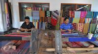 Perajin menenun kain songket menggunakan peralatan tradisional di sentral kerajinan songket Patuh, Desa Sukarara, Lombok Tengah, Selasa (13/10). Desa Sukarara menjadi salah satu penghasil kain tenun khas suku Sasak, Lombok. (Liputan6.com/Gempur M Surya)