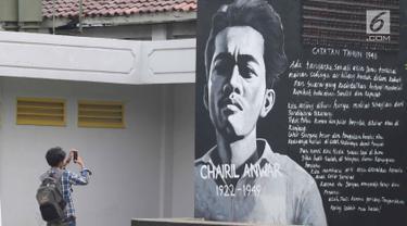 Seorang pengunjung mengabadikan mural penulis Chairil Anwar Taman Ismail Marzuki, Jakarta, Selasa (13/11). Mural tersebut dibuat dalam rangka memeriahkan Hari Pahlawan. (Liputan6.com/Immanuel Antonius)