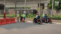 Petugas mengalihkan pengendara sepeda motor yang akan melintasi proyek pembangunan jalur kereta Light Rail Transit (LRT) di Jalan Setiabudi Tengah, Jakarta, Senin (17/6/2019). Jalan Setiabudi Tengah ditutup untuk memberi ruang terkait pengerjaan konstruksi jalur LRT. (Liputan6.com/Herman Zakharia)