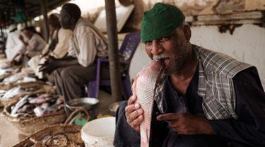 Pedagang ikan bercanda menggigit seekor ikan ketika ia difoto di sebuah pasar ikan di dekat Sungai Nil, di kota kembar Khartoum, Omdurman (24/6/2019). Omdurman merupakan kota terbesar di Sudan memiliki jumlah penduduk sebanyak 1,2 juta jiwa (1993). (AFP Photo/Yasuyoshi Chiba)