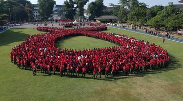 Lebih dari 4 ribu orang membentuk formasi pita merah sebagai simbol AIDS jelang Hari AIDS Sedunia. (Foto: Humas Kemenkes)