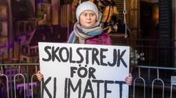 Patung lilin aktivis lingkungan asal Swedia, Greta Thunberg memegang sebuah plakat selama presentasinya di Museum Panoptikum di Hamburg, Jerman, Rabu (29/1/2020). Patung lilin Thunberg dikabarkan adalah yang pertama di museum yang akan berganti pakaian saat musim berubah. (Markus Scholz/dpa/AFP)