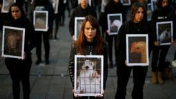 Sejumlah aktivis dari Igualdad Animal mebawa poster bergambar hewan saat melakukan aksi protes di di Madrid, Spanyol (10/12). Mereka bergerak dalam organisasi non-profit yang tujuannya ingin menyetarakan hak binatang. (Reuters/Javier Barbancho)