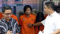 Vokalis grup band Zivilia, Zulkifli alias Zul (tengah) diperlihatkan petugas Ditresnarkoba Polda Metro Jaya, Jakarta, Jumat (8/3). Zul ditangkap terkait penyalahgunaan narkotika di kawasan Jakarta Utara, Kamis (28/2). (Liputan6.com/Helmi Fithriansyah)