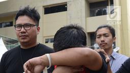 Tersangka berinisial MIK penyebar hoax surat suara tercoblos menutupi wajahnya saat digiring petugas di Polda Metro Jaya, Jakarta, Jumat (11/1). MIK ditangkap sekitar pukul 22.30 WIB, pada 6 Januari. (Merdeka.com/Imam Buhori)