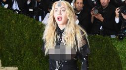 Ekspersi Madonna saat tiba menghadiri ajang Met Gala 2016 di Metropolitan Museum of Art, New York, Senin (2/5). Bertemakan 'Manus x Machina: Fashion In An Age of Technology', Madonna tampil dengan busana transparan. (AFP/Larry Busacca)